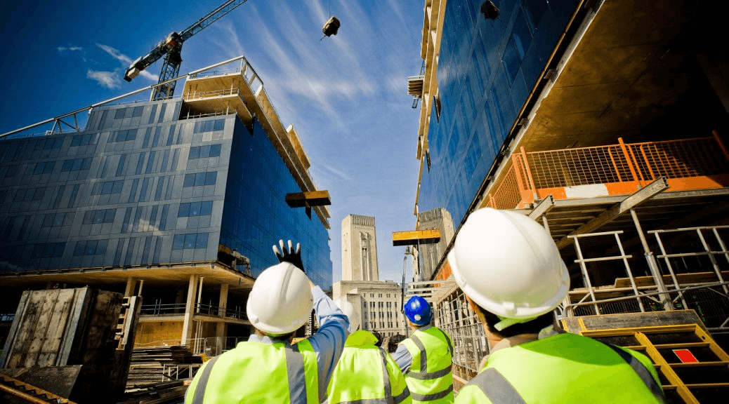 dois homens de colete amarelo a analisarem dois edifícios a serem construídos